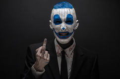 Terrible clown and Halloween theme: Crazy blue clown in black suit isolated on a dark background in the studio Stock Images
