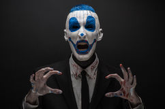 Terrible clown and Halloween theme: Crazy blue clown in black suit isolated on a dark background in the studio Royalty Free Stock Photography