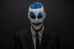 Terrible clown and Halloween theme: Crazy blue clown in black suit isolated on a dark background in the studio Stock Photos