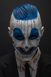 Terrible clown and Halloween theme: Crazy blue clown in black suit isolated on a dark background in the studio. Terrible clown and Halloween theme: Crazy blue royalty free stock photo
