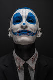 Terrible clown and Halloween theme: Crazy blue clown in black suit isolated on a dark background in the studio Stock Image