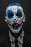 Terrible clown and Halloween theme: Crazy blue clown in black suit isolated on a dark background in the studio Stock Photo