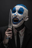 Terrible clown and Halloween theme: Crazy blue clown in a black suit with a knife in his hand isolated on a dark background in the Stock Photography