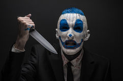 Terrible clown and Halloween theme: Crazy blue clown in a black suit with a knife in his hand isolated on a dark background in the Stock Photos