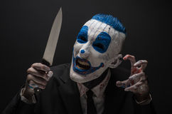 Terrible clown and Halloween theme: Crazy blue clown in a black suit with a knife in his hand isolated on a dark background in the Royalty Free Stock Photography