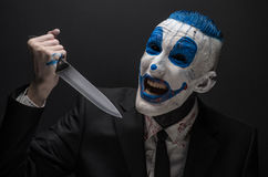 Terrible clown and Halloween theme: Crazy blue clown in a black suit with a knife in his hand isolated on a dark background in the Royalty Free Stock Photos