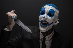 Terrible clown and Halloween theme: Crazy blue clown in a black suit with a knife in his hand isolated on a dark background in the Stock Image