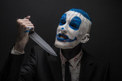 Terrible clown and Halloween theme: Crazy blue clown in a black suit with a knife in his hand isolated on a dark background in the Royalty Free Stock Images