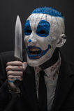 Terrible clown and Halloween theme: Crazy blue clown in a black suit with a knife in his hand isolated on a dark background in the Stock Photo