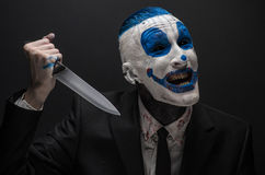 Terrible clown and Halloween theme: Crazy blue clown in a black suit with a knife in his hand isolated on a dark background in the Royalty Free Stock Image