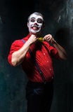 Terrible clown and Halloween theme: Crazy red clown in a shirt with suspenders. On a dark background Royalty Free Stock Images
