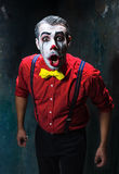 Terrible clown and Halloween theme: Crazy red clown in a shirt with suspenders. On a dark background Royalty Free Stock Photography