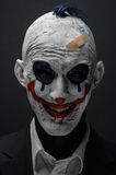 Terrible clown and Halloween theme: Crazy terrible blue clown in black suit isolated on a dark background in the studio. Terrible clown and Halloween theme royalty free stock photo