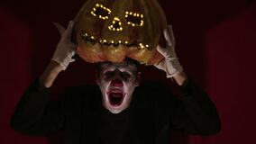 Scary man in the makeup of a clown holds a pumpkin for Halloween and puts it on his head.Terrible clown puts on a mask