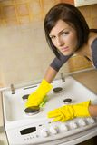 Terrible dirt. Young woman in yellow rubber gloves cleaning cooker. Looking at camera. Front view royalty free stock images