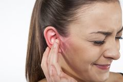 Terrible ear pain, young woman Stock Photo