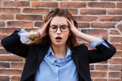 Terrible headache. Portrait of looking tired business woman in smart casual wear touching her head with hands. Terrible headache. Portrait of looking tired Royalty Free Stock Photography