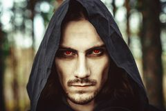 Terrible in the hood. The vampire in the hood with glowing eyes in the forest Royalty Free Stock Photography