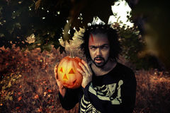 Terrible man. Human zombies holding a pumpkin in her hands. Symbol of the holiday Halloween. Royalty Free Stock Photos