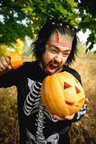 Terrible man. Human zombies holding a pumpkin in her hands. Symbol of the holiday Halloween. Royalty Free Stock Photography