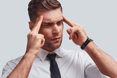 Terrible pain. Frustrated young man in full suit touching his head with hands while standing against grey background Royalty Free Stock Photos
