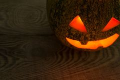 A terrible pumpkin on the holiday of Halloween on the old tree table. With a place for the inscription Royalty Free Stock Photos