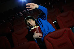 Terrible scene. Young man is terrified by the scene seen on the screen in cinema hall Royalty Free Stock Photography