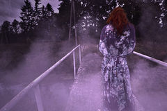 A terrible sinister woman is standing on the bridge at night in a fog Stock Image