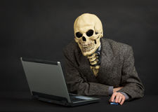 Terrible skeleton sits at black office with laptop Stock Photos