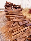 Terrible smell pile of extracted old wooden ties. Old oiled used oak railway sleepers stored Stock Photography