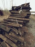 Terrible smell pile of extracted old wooden ties. Old oiled used oak railway sleepers stored Stock Photo