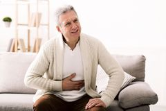 Terrible stomachache. Senior man hugging his belly, suffering from pain