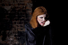 Terrible vampire woman in red cloak Royalty Free Stock Photography