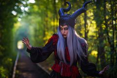 Terrible woman with black horns silver hair amazing makeup in the tunnel of forest with rails close up Royalty Free Stock Photos