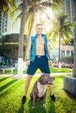 Terrier de pitbull américain d'homme et de chien détendant au parc au coucher du soleil Image stock