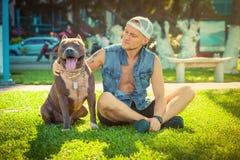 Terrier de pitbull américain d'homme et de chien détendant au parc embrassant et étreignant Image libre de droits