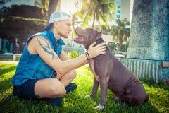 Terrier de pitbull américain d'homme et de chien détendant au parc embrassant et étreignant Photo libre de droits