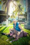 Terrier de pitbull américain d'homme et de chien détendant au parc embrassant et étreignant Photos libres de droits