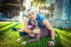 Terrier de pitbull americano del hombre y del perro que se relaja en el parque que abraza y que abraza foto de archivo