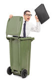 Terrified businessman hiding in a trash can stock photography