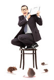 Terrified businessman standing on chair defending himself from r Royalty Free Stock Image