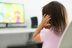 A terrified child, afraid of the loud sounds from the television. Autism royalty free stock image