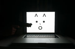 Terrified computer face threatened by cyber criminal Stock Images