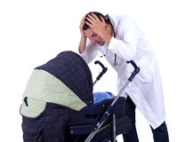 Terrified doctor looking to baby buggy Stock Image