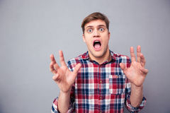 Terrified frightened young man screaming with open mouth. Portrait of terrified frightened young man in checkered shirt screaming with open mouth over grey Stock Images
