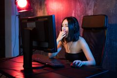 Terrified gamer plays games on your computer. An emotional young woman in the headphones plays games on a computer stock photo