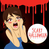 Terrified Halloween Woman. Terrified woman screaming over bloody background with the text Scary Halloween on a full moon Stock Image