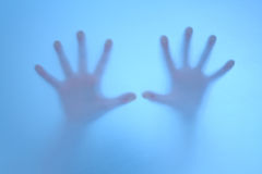 Terrified hands on  frosted glass. Hands calling for help on frosted glass Stock Image