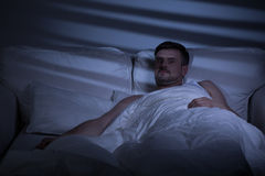 Terrified man in bed. Woke up because of nightmare Royalty Free Stock Images