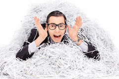 Terrified man covered in a pile of shredder paper stock photography